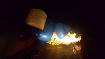 A giant inflatable advertising clown blocked Mill Rd after wild winds sent it airborne over a fence. Photo / Pukekohe Fire