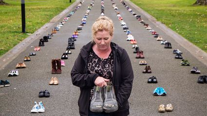 Diane Hall holds the workboots of her husband Jake, who died from suicide in 2014.