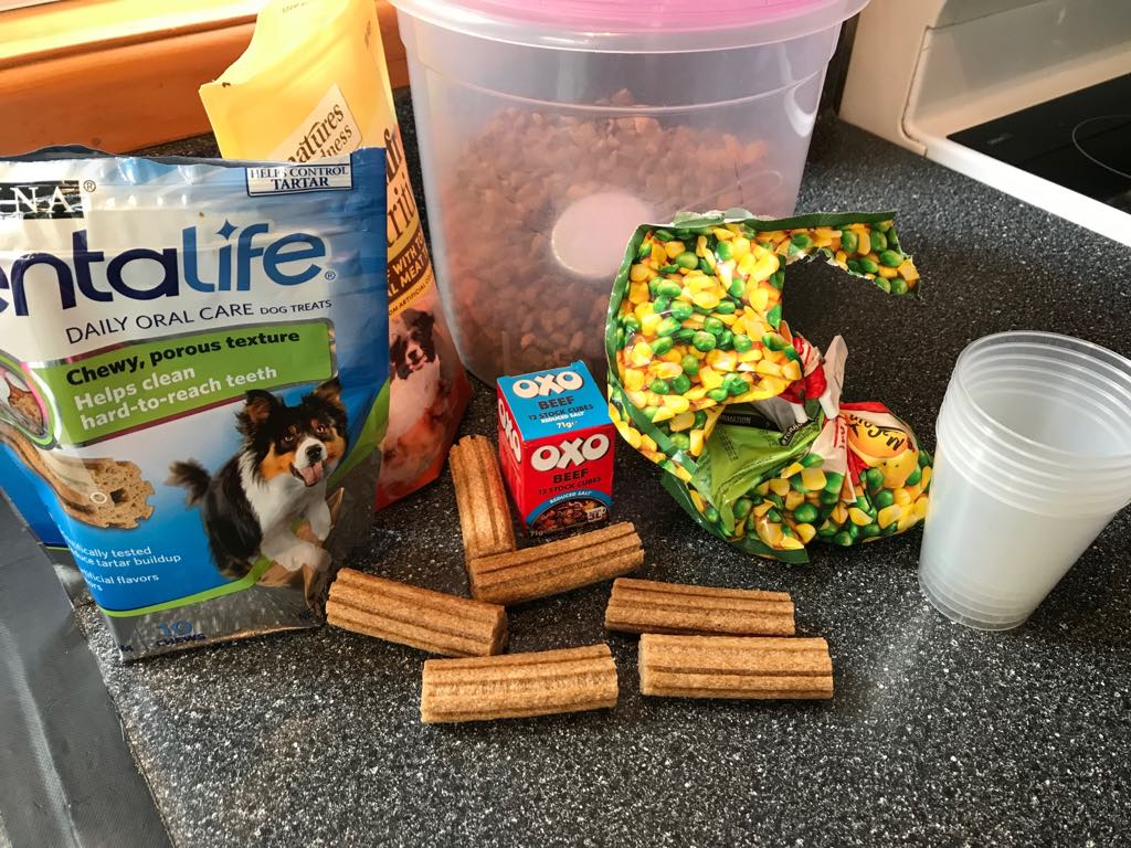 Ingredients we chose to use. Beef stock cubes, peas&corn, dog nuts and treats. Plastic cups to set in or you could use ice trays for small pupsicles or if you have the actual plastic ice block containers go for that.