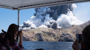 White Island erupts as a tourist boat leaves the island yesterday. Photo / Michael Schade
